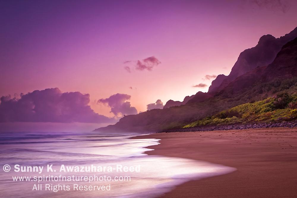 Pastel sunset sky over rugged mountains at Napali Coast, Kalalau Beach, Na Pali Coast State Park, Kauai, Hawaii.