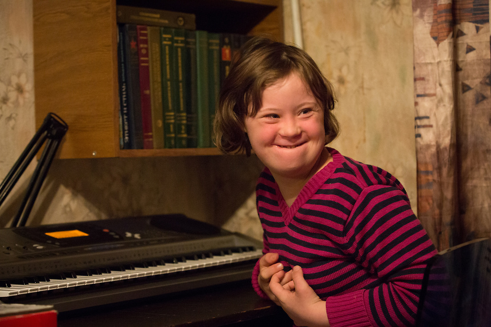 CAPTION: Eva, who has Downs Syndrome, derives great joy from music. One of the things that makes her happiest is playing with the electric organ at home. LOCATION: St Petersburg, Russia. INDIVIDUAL(S) PHOTOGRAPHED: Eva Nikolayeva.