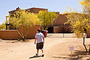 """22 MAY 2011 - SCOTTSDALE, AZ:  A man walks back to the house after putting up a """"No Trespassing"""" sign in front of a home reportedly owned by Sarah Palin in Scottsdale, AZ. According to the Arizona Republic, Sarah Palin and her husband Todd Palin, bought the 8,000 square foot home for $1.695 million cash. The newspaper said the Palin's name does not appear on the paperwork and the home was bought by Safari Investments LLC out of Delaware. The paper said the deal """"appears designed to cloak the identity of a high-profile buyer."""" The home has six bedrooms, five bathrooms, a six car garage, swimming pool, spa, home theater, wine cellar and children's """"jungle gym"""" in the backyard. The home is surrounded by a tall wall with an electronic gate. Phoenix TV stations have reported that a black SUV with Alaska license plates has been seen entering and leaving the compound. People in the house have refused to comment on who owns the home. Neither Palin nor her husband have been seen at the home since news of the sale broke Saturday, May 21.   Photo by Jack Kurtz"""