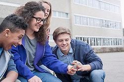 University students enjoying with mobile phone in campus, Bavaria, Germany