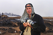 Peter Menzel photographing oil well fires at Rumaila Oil Field, in southern Iraq. The wells were set on fire with explosives placed by retreating Iraqi troops when the US and UK invasion began. Seven or eight wells were set ablaze but at least one other was detonated but did not ignite. The Rumaila field is one of Iraq's biggest oil fields with five billion barrels in reserve. Many of the wells are 10,000 feet deep and produce huge volumes of oil and gas under tremendous pressure, which makes capping them very difficult and dangerous. This well was of relatively low volume. Rumaila is also spelled Rumeilah.