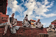 Nepali men realx and chat on a brick temple in Kathmandu's world Heriatge listed Durbar Square.