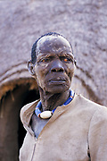 A Dinka man with dry weather beaten wrinkled face, wearing a large blue decorative necklace, South Sudan, 1997