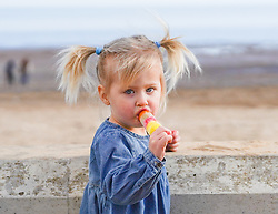 © Licensed to London News Pictures. 27/02/2021. Bridlington, UK. Millie,2, enjoys an ice cream on Bridlington beach, East Yorkshire, in mild spring weather. Meteorologists forecast the temperatures are expected to top 14 degrees celsius  this weekend.Photo credit: Ioannis Alexopoulos/LNP