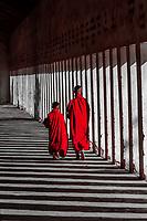 Two novice monks walking down a corridor in the Shwezigon Pagoda, Bagan (Pagan), Burma (Myanmar).