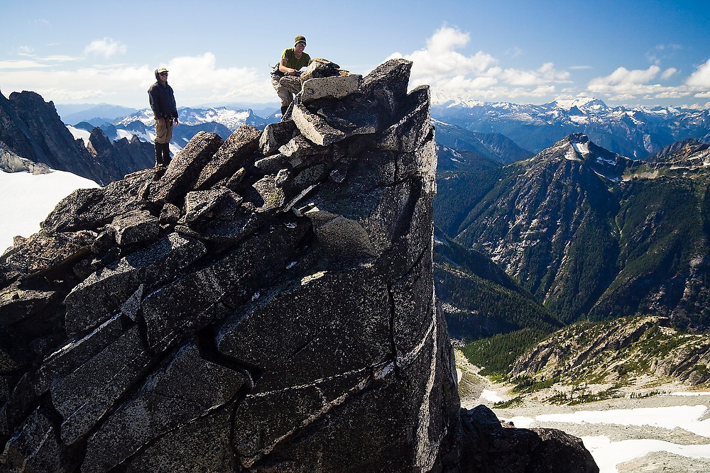 Jim Prager and Brian Polagye stand on the edge of a cliff below the summit of remote Primus Peak, North Cascades National Park, Washington.