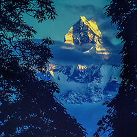 Macchapucchare Peak glows in a sunset over the Himalaya in Nepal.