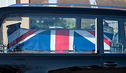 © Licensed to London News Pictures. 27/02/2021. Marston Moretaine, UK. A hat and a sword sit on the coffin as the The funeral cortege carrying the coffin of Captain Sir Tom Moore passes members of the public in his home town of Marston Moretaine, on it's way to Bedford Crematorium for a funeral service. Captain Tom, who raised £32 million pounds for the NHS by walking laps of his garden during Coronavirus lockdown, died in hospital aged 99. Photo credit: Ben Cawthra/LNP