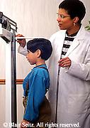 Medical African American Nurse Weights Hispanic Boy at Urban Clinic