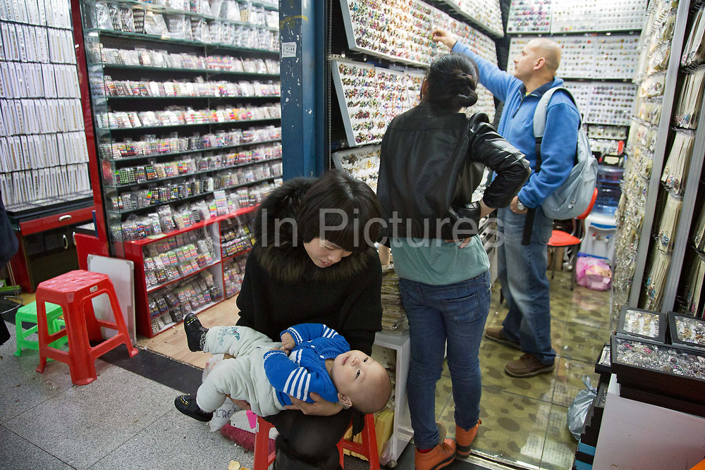 A woman tickles a baby while waiting for customers at the China Commodities City in Yiwu, Zhejiang Province, China on 06 March  2013. The city of Yiwu is known as one of China's largest trading centers for small merchandise and light industry, drawing buyers from around the world. Uncertain global demand, a stronger yuan currency and rising labour costs have taken their toll on Chinese exporters, but analysts believe sales could pick up modestly in 2014 due to improved demand from the United States and Europe.
