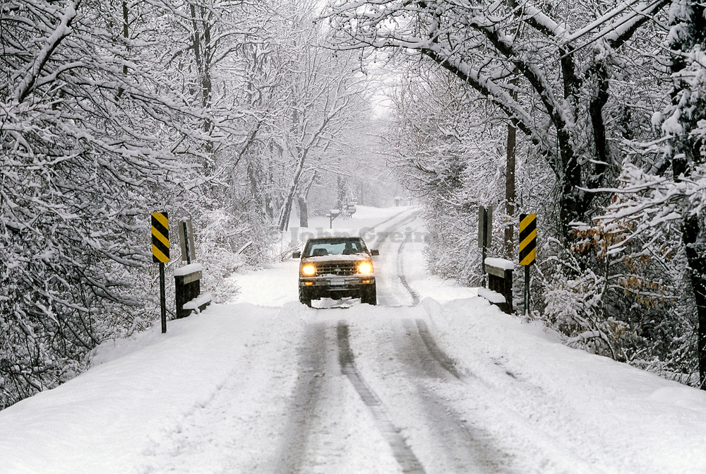 Sports utility vehicle crossing an icy, snow covered road.