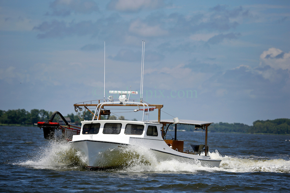 03 July 2013. St Michael's, Maryland.<br /> Clam boats on their way out of the marina.<br /> Charlie Varley/varleypix.com