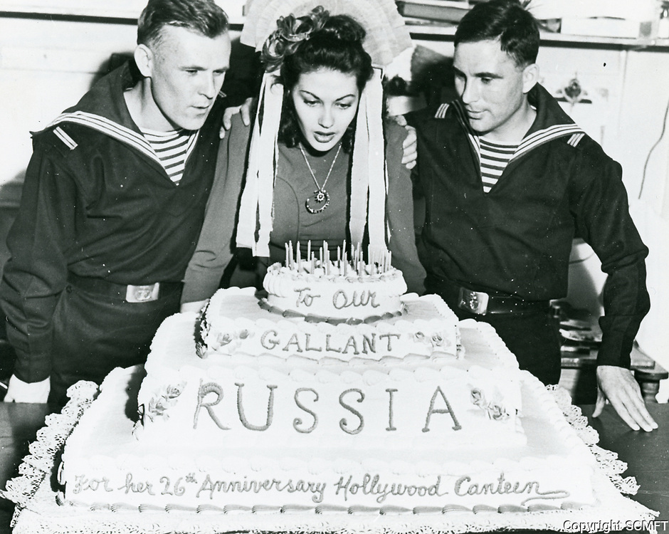 1944 Yvonne Carlo blows out the candles on a cake, at the Hollywood Canteen, celebrating Russia's adoption of its constitution.