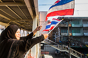 18 FEBRUARY 2014 - BANGKOK, THAILAND: A Thai Muslim anti-government protestor waves Thai flags from a pedestrian overpass in Bangkok. Anti-government protestors aligned with Suthep Thaugsuban and the People's Democratic Reform Committee (PDRC) clashed with police Tuesday. Protestors opened fire on police with at rifles and handguns. Police returned fire with live ammunition and rubber bullets. The Bangkok Metropolitan Administration's Erawan Emergency Medical Centre reported that three civilians and a policeman were killed and 64 others were injured in the clashes between police and protesters.    PHOTO BY JACK KURTZ