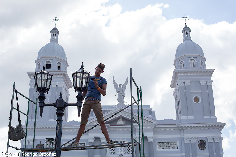 A young man applies paint to a street light across from the cathedral of Santiago de Cuba, Cuba, on December 26, 2014.