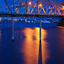 Lights reflect in the Pisctaqua River below the Memorial Bridge in Portsmouth, New Hampshire. Lens baby.