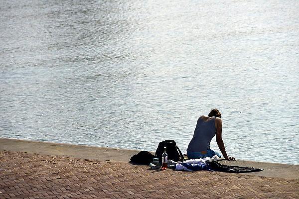 Nederland, Arnhem, 13-3-2014 Een jonge vrouw zit op deze mooie en warme voorjaarsdag op de rand van de kade langs de rivier de Rijn, de Rijnkade in de zon. Ze heeft een fles wijn en hapjes bij zich om een buiten, openlucht, lunch, picknick te houden. Foto: Flip Franssen/Hollandse Hoogte