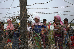 September 6, 2017 - Mongdaw, Myanmar - Rohingya people wait to cross the border at Mongdaw, Myanmar on September 6, 2017.  Rohingya are a Muslim ethnic minority that the government of Buddhist-majority Myanmar largely does not recognise as citizens...Violence erupted in Myanmars Rakhine state on Aug. 25 when the countrys security forces launched an operation against the Rohingya Muslim community. It triggered a fresh influx of refugees towards neighboring Bangladesh, though the country sealed off its border to refugees. (Credit Image: © Mushfiqul Alam/NurPhoto via ZUMA Press)