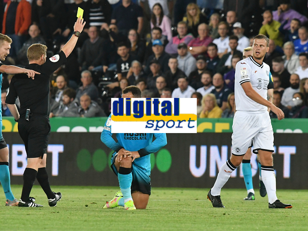 Football - 2021 / 2022  EFL Sky Bet Championship - Swansea City vs Millwall - Liberty Stadium - Wednesday 15th September 2021<br /> <br /> referee Mr John Busby  shows the yellow card after Mason Bennett Millwall brought down by  Ryan Bennett Swansea City<br /> <br /> COLORSPORT/WINSTON BYNORTH