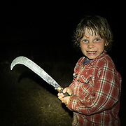 A child jokingly threatens the viewer, holding a machete in his hand.