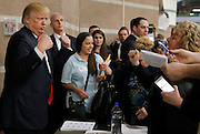 Republican U.S. presidential candidate Donald Trump flexes his muscles as he talks with caucus participants while visiting a Nevada Republican caucus site at Palo Verde High School in Las Vegas, Nevada February 23, 2016.   REUTERS/Jim Young
