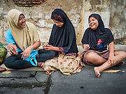 24 SEPTEMBER 2015 - BANGKOK, THAILAND:  Girls relax in front of Haroon Mosque before the celebration of Eid al-Adha at Haroon Mosque in Bangkok. Eid al-Adha is also called the Feast of Sacrifice, the Greater Eid or Baqar-Eid. It is the second of two religious holidays celebrated by Muslims worldwide each year. It honors the willingness of Abraham to sacrifice his son, as an act of submission to God's command. Goats, sheep and cows are sacrificed in a ritualistic manner after services in the mosque. The meat from the sacrificed animal is supposed to be divided into three parts. The family retains one third of the share; another third is given to relatives, friends and neighbors; and the remaining third is given to the poor and needy.    PHOTO BY JACK KURTZ