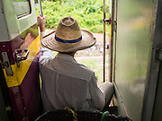 20 MARCH 2015 - KABIN BURI, PRACHINBURI, THAILAND: A man sits in the door of a 3rd class train going to Kabin Buri. The State Railways of Thailand (SRT), established in 1890, operates 4,043 kilometers of meter gauge track that reaches most parts of Thailand. Much of the track and many of the trains are poorly maintained and trains frequently run late. Accidents and mishaps are also commonplace. Successive governments, including the current military government, have promised to upgrade rail services. The military government has signed contracts with China to upgrade rail lines and bring high speed rail to Thailand. Japan has also expressed an interest in working on the Thai train system. Third class train travel is very inexpensive. Many lines are free for Thai citizens and even lines that aren't free are only a few Baht. Many third class tickets are under the equivalent of a dollar. Third class cars are not air-conditioned.   PHOTO BY JACK KURTZ