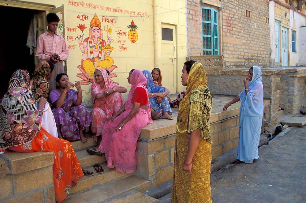 India, Rajasthan, Jaisalmer. Hindu women in saris chat on porch below painted Ganesh.