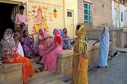 India, Rajasthan, Jaisalmer. Hindu women in saris chat on porch below painted Ganesh.