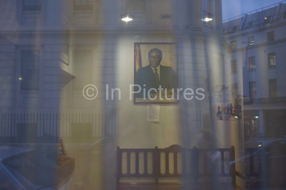 Framed portrait of Zimbabwe President Robert Mugabe through window of London embassy. Just as evening light is fading, we look through net curtains to the President's formal photograph that adorns embassies and high commissions around the world. Seating for those awaiting visas etc. is seen below the frame and London streets reflected in the distance. Controversial Robert Gabriel Mugabe has served since 31 December 1987. As one of the leaders of the rebel groups against white minority rule, he was elected as Prime Minister, head of government, in 1980, and served in that office until 1987, when he became the country's first executive head of state. He has led the Zimbabwe African National Union – Patriotic Front (ZANU–PF) since 1975.
