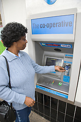 Older woman withdrawing money from a cash machine,