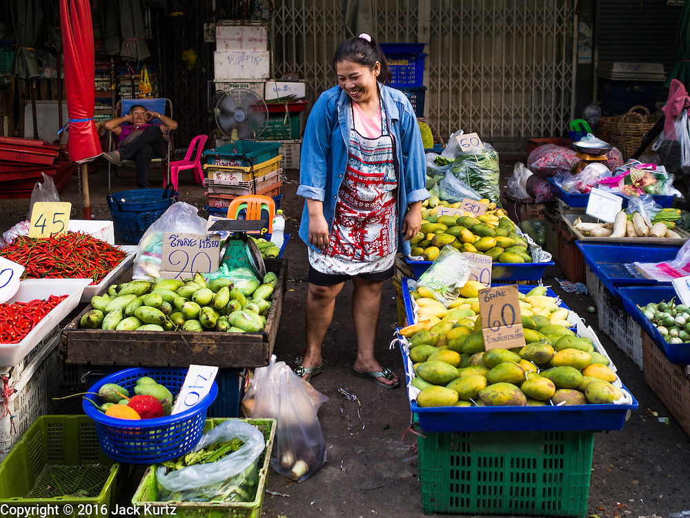 """12 JANUARY 2016 - BANGKOK, THAILAND:      A mango seller in Khlong Toey Market in Bangkok. Khlong Toey (also called Khlong Toei) Market is one of the largest """"wet markets"""" in Thailand. The market is located in the midst of one of Bangkok's largest slum areas and close to the city's original deep water port. Thousands of people live in the neighboring slum area. Thousands more shop in the sprawling market for fresh fruits and vegetables as well meat, fish and poultry.         PHOTO BY JACK KURTZ"""