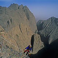 Mountaineer Sam Lightner, Jr. climbs treacherous conglomerate rock on Shipton's Arch in the arid Kara Tagh Mountains next to the Taklimakan Desert near Kashagar (Kashi) in Xinjiang Province, China. Later the expedition crossed the range by descending the dangerous and unexplored slot canyon behind him.