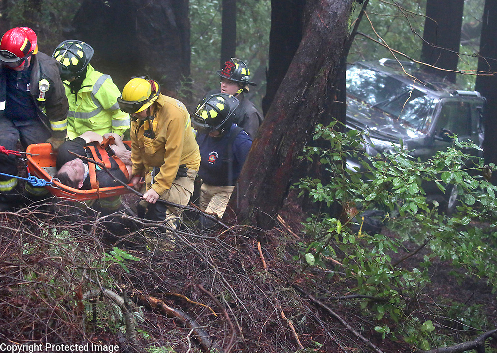 Zayante, California firefighters use a Stokes basket to bring a Scott Hall, 50, of Felton, up a ravine to safety after he drove his Toyota 4Runner down an embankment off of Lake Blvd. in Lompico. Hall was transported by ambulance for medical treatment to Dominican Hospital where he was also arrested on suspicion of driving under the influence. <br /> Photo by Shmuel Thaler <br /> shmuel_thaler@yahoo.com www.shmuelthaler.com