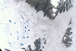 """View Image Comparison<br /> View Both Images<br /> Zachariæ Isstrøm has become the latest Greenland glacier to undergo rapid changes in a warming world. Research published November 2015 in Science found that Zachariæ Isstrøm broke loose from a stable position in 2012 and entered a phase of accelerated retreat.<br /> The consequences will be felt for decades to come. The reason? Zachariæ Isstrøm is big. It drains ice from a 91,780 square kilometer (35,440 square mile) area of northeast Greenland. That's about 5 percent of the Greenland Ice Sheet. The glacier holds enough water to raise global sea level by more than 46 centimeters (18 inches) if it were to melt completely. It is already shedding billions of tons of ice into the far North Atlantic each year.<br /> """"North Greenland glaciers are changing rapidly,"""" said lead author Jeremie Mouginot of the University of California, Irvine (UCI). """"The shape and dynamics of Zachariæ Isstrøm have changed dramatically over the last few years. The glacier is now breaking up and calving high volumes of icebergs into the ocean, which will result in rising sea levels for decades to come.""""<br /> The change is apparent in the images above. The top image was acquired by the Enhanced Thematic Mapper Plus (ETM+) on Landsat 7 on August 5, 1999, when the glacier was stable. The second image was acquired on August 2, 2015, with the Operational Land Imager (OLI) on Landsat 8. The second image shows how the ice shelf and glacier have melted and retreated substantially. Turn on the image comparison tool to see the difference.<br /> As of 2015, the glacier is losing 5 billion tons of ice every year. The time-lapse animation above shows the glacier's retreat during the 2015 melt season. The animation is composed of 26 natural-color images acquired by Landsat 8 from May 19 through October 1, 2015.<br /> To better understand the changes taking place at Zachariæ Isstrøm, Mouginot and his colleagues from NASA's Jet Propulsion Laboratory (JPL), and"""