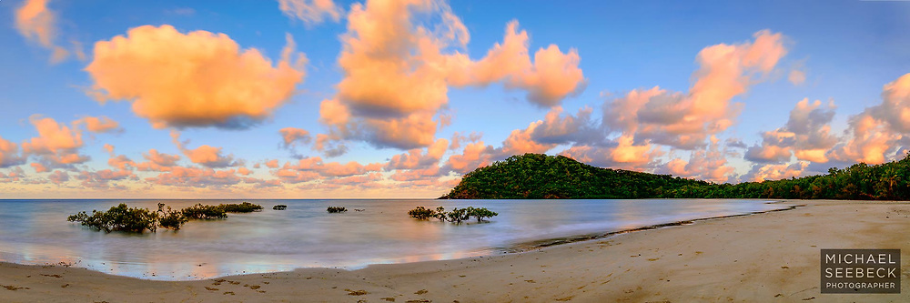 Sunset illuminates scattered cumulus clouds over Cape Tribulation beach, with gentle waves breaking on the pristine beach.