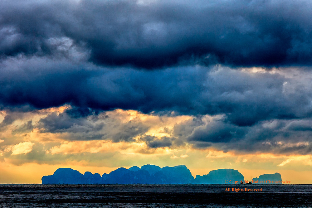 Layers of Blue: Storm clouds mount over the equally blue island silhouette of Phi Phi, from Ko Lanta Thailand.