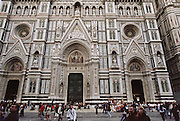 Façade of the Duomo with tourists, in Florence, Italy.