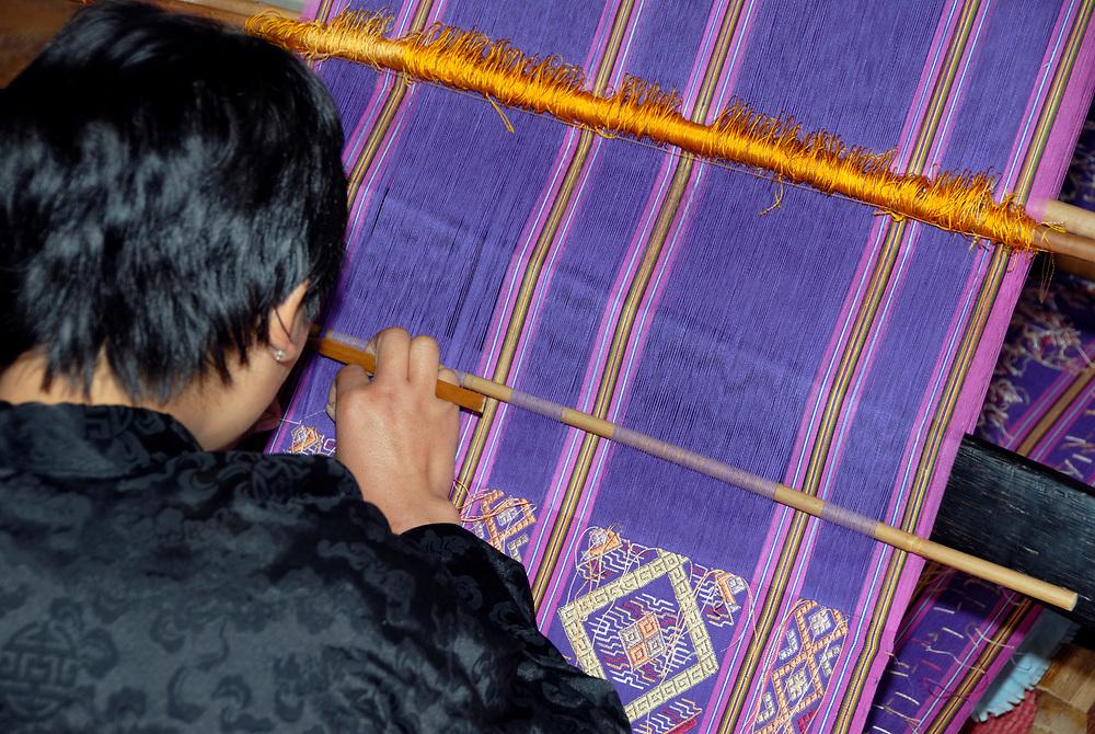 A young lady weaves a length of beautifully intricate silk cloth using a backstrap loom at the National Handloom Development Centre. Khaling, Trashigang, Bhutan, Druk Yul. 20 November 2007