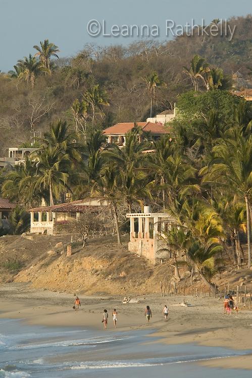 Sayulita, Mexico - the beach atracts people to walk along the shore, while homes rise up along the hillside.