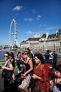 Tourists cross Westminster bridge by the River Thames at Westminter, London. With the iconic London Eye behind this is one of the busiest areas for tourism in the city.