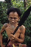PENAN, MALAYSIA. Sarawak, Borneo, South East Asia. Penan with blowpipe. Beard and moustache.Tropical rainforest and one of the world's richest, oldest eco-systems, flora and fauna, under threat from development, logging and deforestation. Home to indigenous Dayak native tribal peoples, farming by slash and burn cultivation, fishing and hunting wild boar. Home to the Penan, traditional nomadic hunter-gatherers, of whom only one thousand survive, eating roots, and hunting wild animals with blowpipes. Animists, Christians, they still practice traditional medicine from herbs and plants. Native people have mounted protests and blockades against logging concessions, many have been arrested and imprisoned.