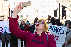 "Anti-transgender feminist Venice Allan, 42, takes a selfie against a backdrop of transgender rights activists demonstrate outside Westminster Magistrates' Court to ""Free the Shewolf"", Tanis Jacob Wolf / aka Tara Flik Wood who is facing a charge of assault by beating of a 60 year old woman at Speaker's Corner in Hyde Park, London in September 2017.<br /> <br /> Wolf/Wood, 26, entered a plea of not guilty and was bailed to appear at Hendon Magistrates' Court in two months' time. London, February 15 2018."