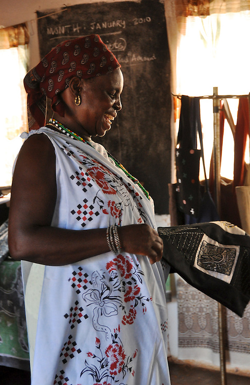 The smiling leader of Twawanani Textiles hods an embroidered and printed textile in their workshop in Limpopo, South Africa