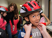 Staff and volunteers from Coca Cola and ExxonMobil help distribute bicycles and helmets for Elves and More to more than 400 children who improved their reading skills at Southmayd Elementary School, December 14, 2013.