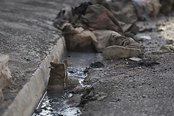 November 11, 2016 - Mosul, Nineveh, Iraq - 11/11/2016. Mosul, Iraq. A boot sits in a gutter and beyond the dead bodies of ISIS extremists, killed four days before by Iraqi forces, are seen in Mosul's Al Intisar district on the south east of the city. The Al Intisar district was taken four days ago by Iraqi Security Forces (ISF) and, despite its proximity to ongoing fighting between ISF and ISIS militants, many residents still live in the settlement without regular power and water and with dwindling food supplies...The battle to retake Mosul, which fell June 2014, started on the 16th of October 2016 with Iraqi Security Forces eventually reaching the city on the 1st of November. Since then elements of the Iraq Army and Police have succeeded in pushing into the city and retaking several neighbourhoods allowing civilians living there to be evacuated - though many more remain trapped within Mosul. (Credit Image: © Matt Cetti-Roberts via ZUMA Wire)