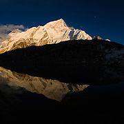 Mount Nuptse and the shoulder of Mount Everest glow in the light of sunset and reflect in a pool in Gorak Shep at the foot of Kala Pattar, Solu-Khumbu Region, Nepal.