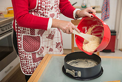 Senior woman pouring dough into a spring form pan, Munich, Bavaria, Germany