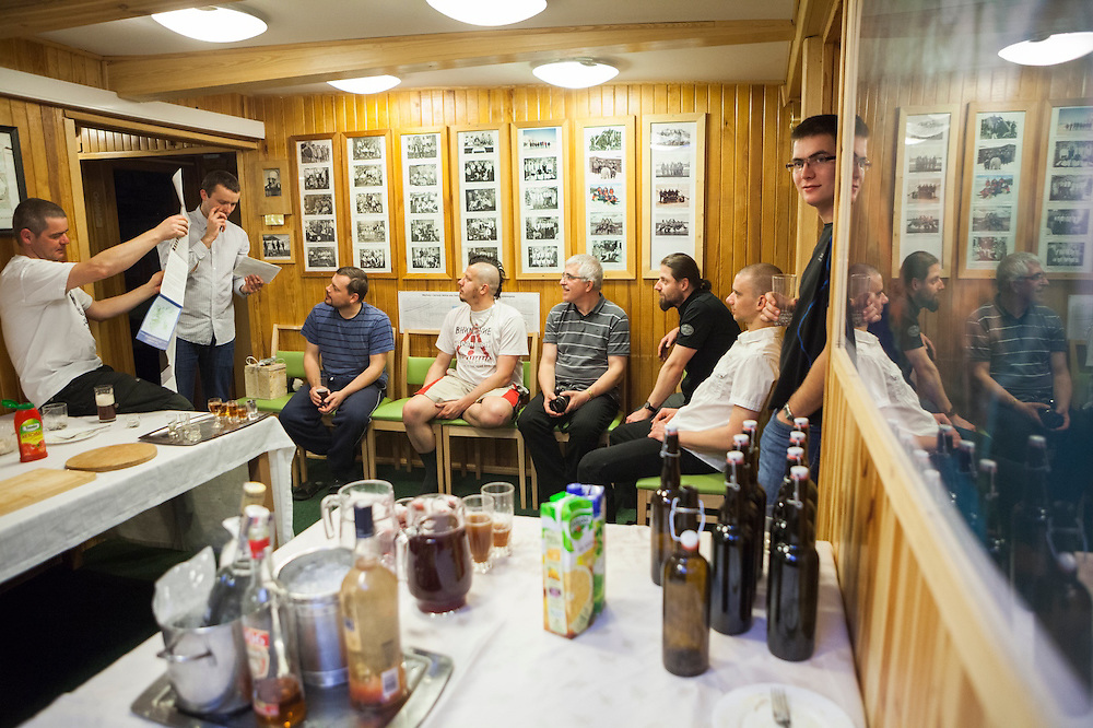 Men discuss field plans over drinks celebrating a birthday at the Polish Polar Station in Hornsund, Svalbard.