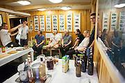 Men discuss field plans over drinks celebrating a birthday at the Polish Polar Station in Hornsund, Svalbard.
